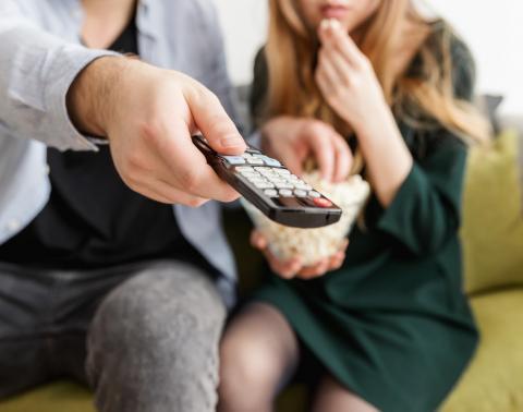beeld van personen in de zetel en een tv remote vast